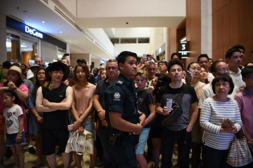 Cảnh sát Singapore đứng trước đám đông muốn quan sát Kim Jong-un tại khách sạn Marina Bay Sands ở Singapore ngày 11/6. Ảnh: AFP.