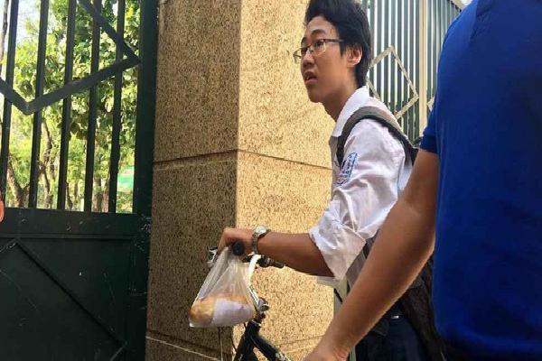 Xót xa cảnh nam sinh tự đạp xe đến trường thi với chiếc bánh mỳ mua vội treo trên ghi-đông chưa kịp ăn