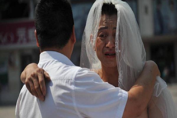Người đàn ông mặc váy cưới đứng đường và câu chuyện khiến ai cũng rớt nước mắt