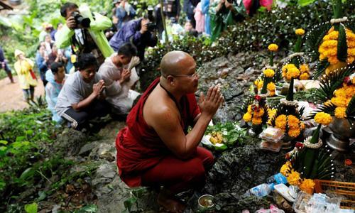 Một nhà sư và thân nhân các cậu bé mắc kẹt cầu nguyện gần khu vực hang Tham Luang trước chiến dịch giải cứu. Ảnh: Reuters.