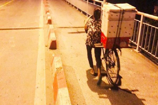 Hình ảnh người phụ nữ khuyết tật gồng mình đẩy chiếc xe bánh mì lên dốc cầu buổi sáng sớm khiến nhiều người thương cảm
