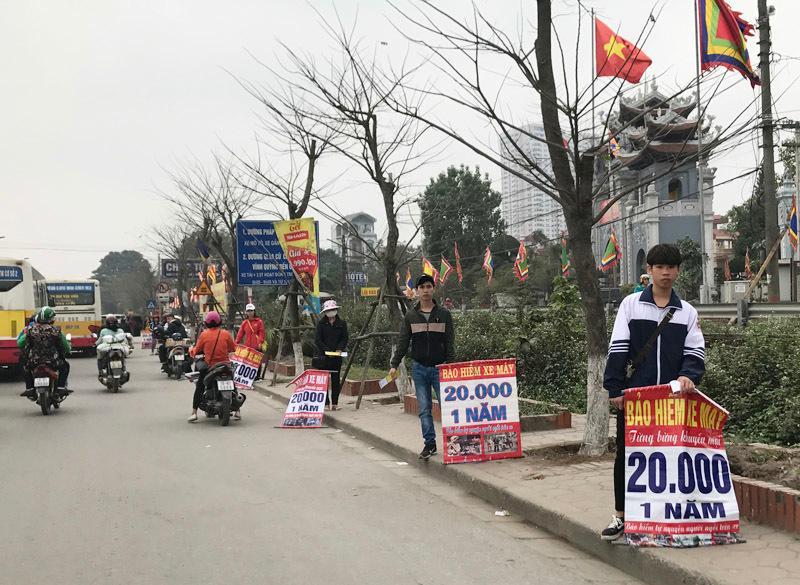 Từ đầu tuần này, dọc đường Giải Phóng xuất hiện hàng chục người bán bảo hiểm giá rẻ chỉ 20 nghìn đồng.