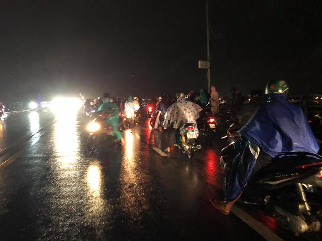 Nhiều người dân dừng lại tại khu vực có chiếc xe máy và hai đôi dép trẻ em trên cầu Thạch Bích. Ảnh: T.Cư.