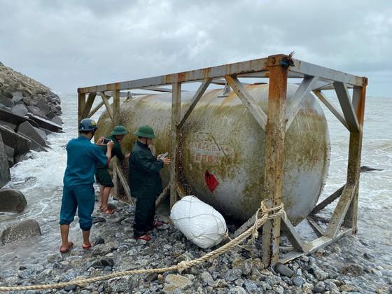 Vật thể lạ có hình dạng bồn chứa, khung sắt bảo vệ, niêm phong được phát hiện tại vùng biển cảng Dung Quất, xã Bình Thuận, huyện Bình Sơn, tỉnh Quảng Ngãi.
