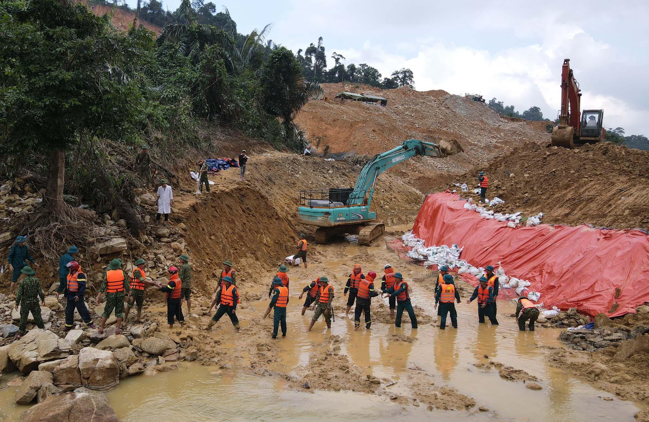 Lực lượng cứu hộ đào kênh phụ dẫn nước Rào Trăng. Ảnh: Đình Hồng.