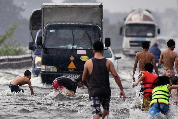 Trai tráng trêu đùa xe cộ đang cố băng qua đường ngập nước