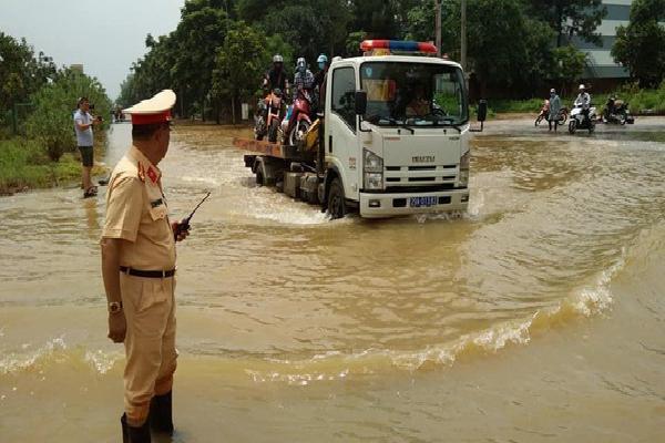 Hà Nội: CSGT dùng xe chuyên dụng giúp dân di chuyển qua vùng ngập úng