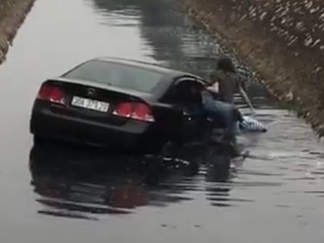 Mất lái vì trời mưa đường trơn trượt, nữ tài xế đã lao thẳng ô tô xuống mương nước đen ngòm