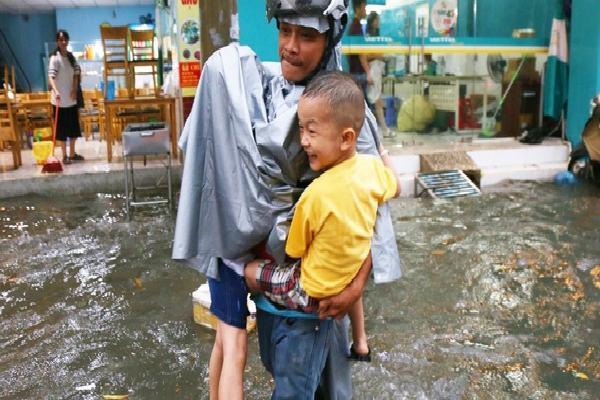 Sài Gòn sau cơn mưa 'khủng', bố mẹ bì bõm lội nước bế con đi học về