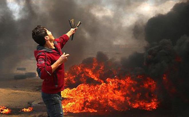 Một người biểu tình Palestine dùng ná bắn vào binh lính Israel.